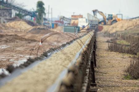 Industrial belt conveyor moving raw materials.