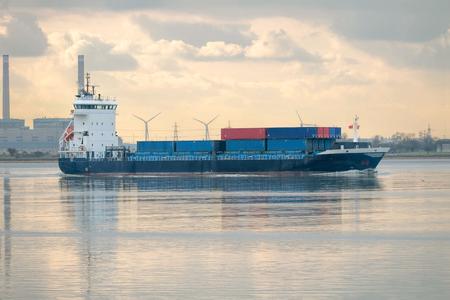 Feeder ship. Cargo vessel on industrial river.