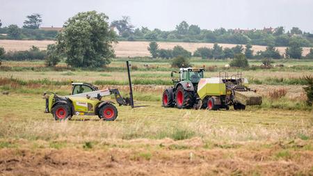 Somerset, UK - July 9, 2016:  Farm vehicles at work in field harvesting hay.