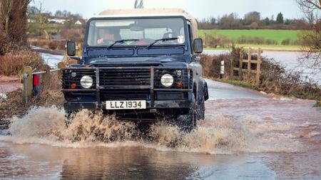 Somerset, UK - February 7, 2016: Vehicle Driving Through Flood Water On UK Road Editorial