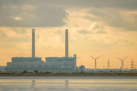 Industrial factory on river with wind turbines at sunset.