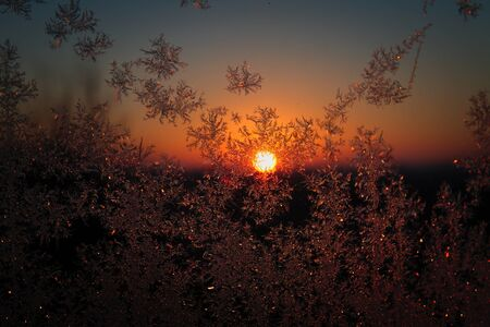 Beautiful Sunset through a Window with Ice Crystals