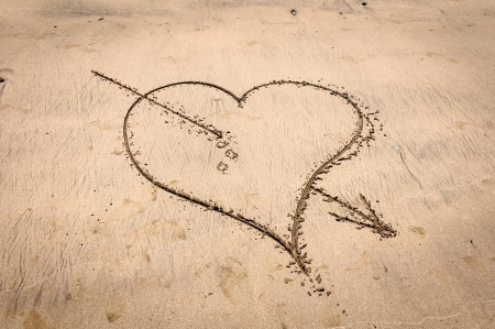 valentine s day beach: Heart pierced by Cupid s arrow drawn in the sand Stock Photo