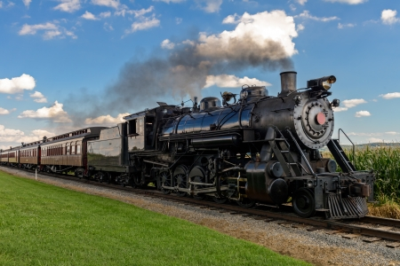 black train: historic steam train passes through the fields Stock Photo