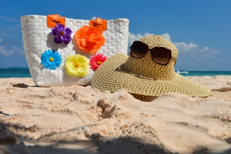 Summer beach bag with straw hat,sunglasses on sandy beach