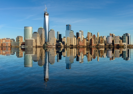 with reflection: Lower Manhattan skyline panorama over East River with reflection and blue sky in New York City