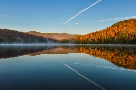 De Bezinningen van de herfst bladeren Kleurrijke herfst bladeren schuur terug te vinden op de kalme wateren van Heart Lake in Lake Placid
