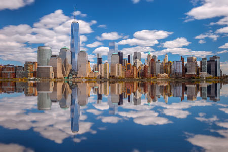 Lower Manhattan skyline panorama over East River with reflection and blue sky