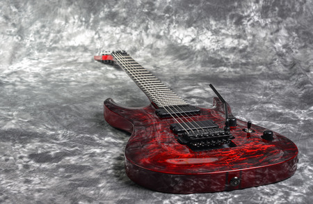 red seven-stringed electric guitar  on white-gray background photo