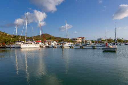 dockyard: Yachts and power boats anchored in crystal clear turquoise waters in the Caribbean