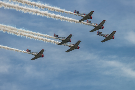 world war ii: NEW WINDSOR, NY - SEPTEMBER 3, 2016: The GEICO Skytypers Air Show Team perform at the New York Airshow at Stewart Int Airport. SNJ-2 World War II era planes fly in formation.