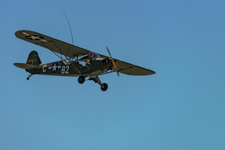 READING, PA - JUNE 3, 2017: PIPER L-4H GRASSHOPPER in flight during World War II reenactment at Mid-Atlantic Air Museum Stock Photo