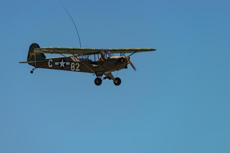 READING, PA - JUNE 3, 2017: PIPER L-4H GRASSHOPPER in flight during World War II reenactment at Mid-Atlantic Air Museum Editorial