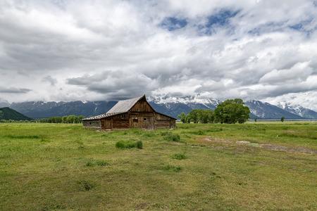 Old mormon barn in Grand Teton Mountains with low clouds. Grand Teton National Park, Wyoming, USA. 版權商用圖片