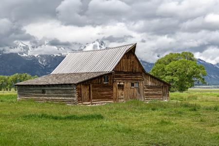 Old mormon barn in Grand Teton Mountains with low clouds. Grand Teton National Park, Wyoming, USA. Stockfoto
