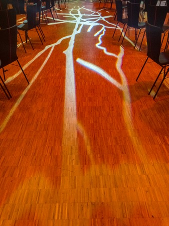 Gobo lighting highlights the floor between aisles of chairs