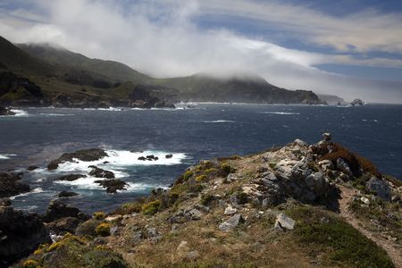 View of the Big Sur coastline in California with fog covering part of the land Stock Photo