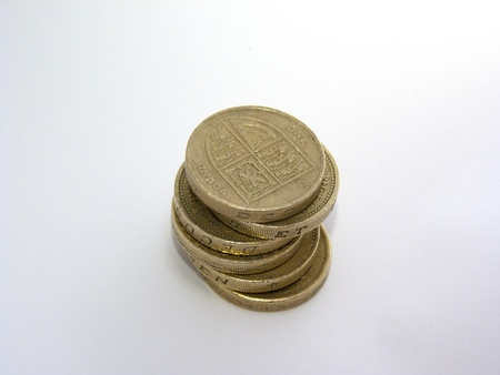 wonky: Pile of 6 British golden pound coins isolated on a white background.