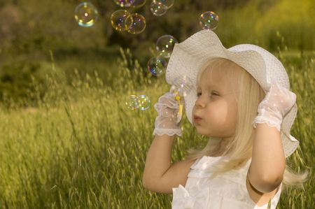 spring hat: Little girl in a white dress and hat blowing soap bubbles in a field Stock Photo