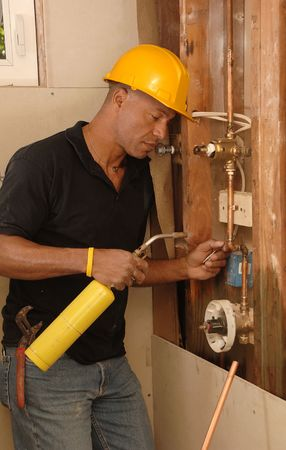 Plumber sweating a copper pipe with a propane torch photo