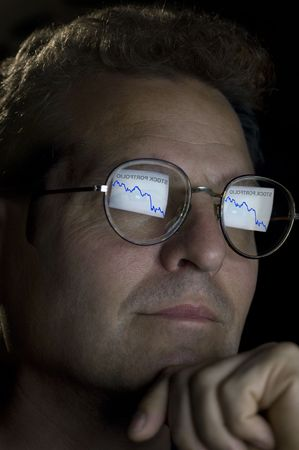 equities: close-up of an investor with an ascending stock portfolio graph reflected in his glasses. Stock Photo