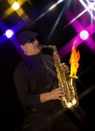 Man playing a flaming saxophone with stage lights in the background Stock Photo - 7039710