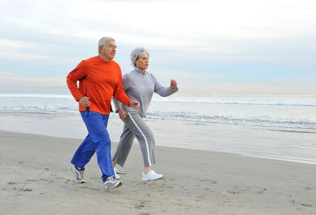 senior woman exercising: Senior couple jogging on the beach in the early morning