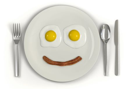 A plate with a frowning face made from two sunny side up eggs and a strip of bacon on a white background photo
