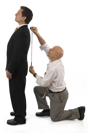 measured: Man getting measured by a tailor on a white background. Stock Photo