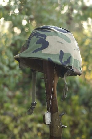 remembrance: Helmet resting on the stock of a rifle with a dog tag hanging on a chain