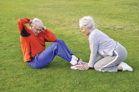 Senior couple doing sit ups on grass Stock Photo