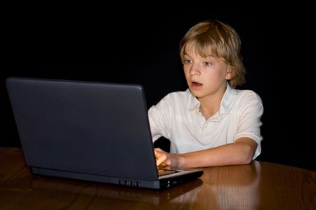 addiction alone: Preteen boy with a mezmerized expression, staring into a computer screen