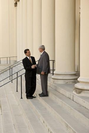 2 人の男性が裁判所のステップで握手
