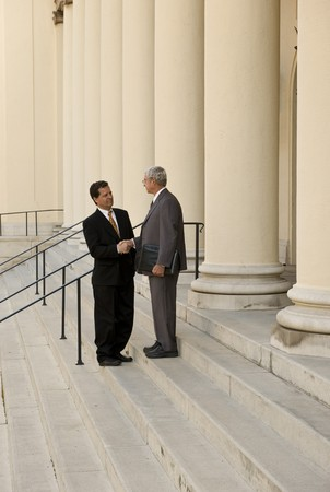 litigation: Two men shaking hands on courthouse steps Stock Photo