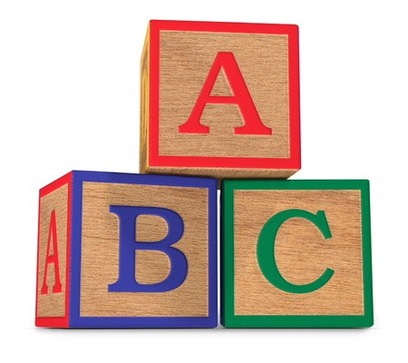 Wooden ABC alphabet blocks stacked on a white background Imagens