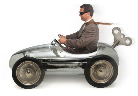 Mn in a wind-up/pedal car on white background Standard-Bild