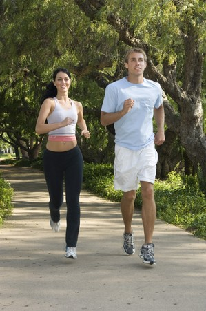 Young, attractive couple jogging in the city park photo