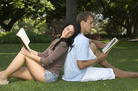 date book: Attractive, young couple sitting back to back, reading books in the park Stock Photo