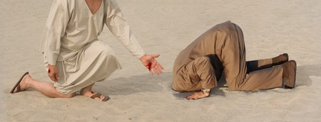 stigmata: Figure with crucifixion wounds extending a hand to another man with his head in the sand Stock Photo