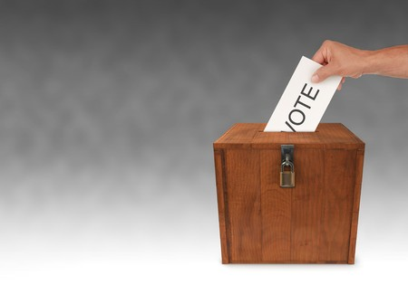 balloting: A mans hand putting an envelope in the slot of a box Stock Photo