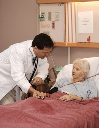 death and dying: doctor visiting senior woman patient in hospice