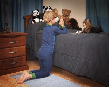 obediencia: muchacho arrodillado junto a la cama diciendo oraciones en pijama