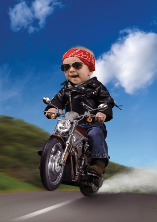 Baby dressed as a biker, popping a wheelie on a motorcycle  photo
