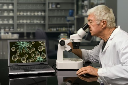 pathologist: Biologist looking through a microscope in a research lab