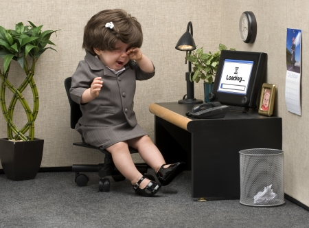Baby dressed in professional office attire crying at her desk photo