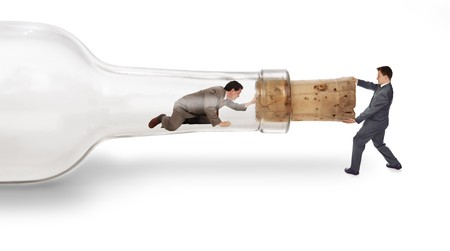 A businessman trapped inside a bottle trying to crawl out through the neck with his partner pulling on the cork from the outside