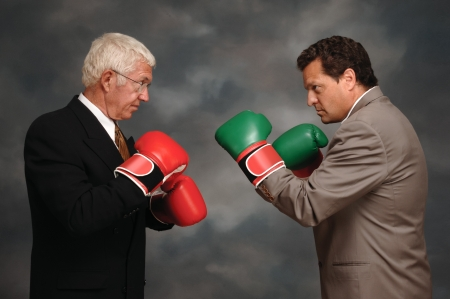 Two businessmen in business suites facing off with boxing gloves Stock Photo - 16947874
