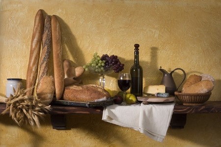 Bread, cheese, wine and grapes against a tuscan plaster wall photo