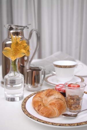 Continental breakfast with croissant, yogurt and coffee in a vertical format photo