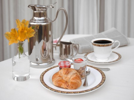 Continental breakfast with a croissant, yogurt and coffee on a white linen tablecloth photo